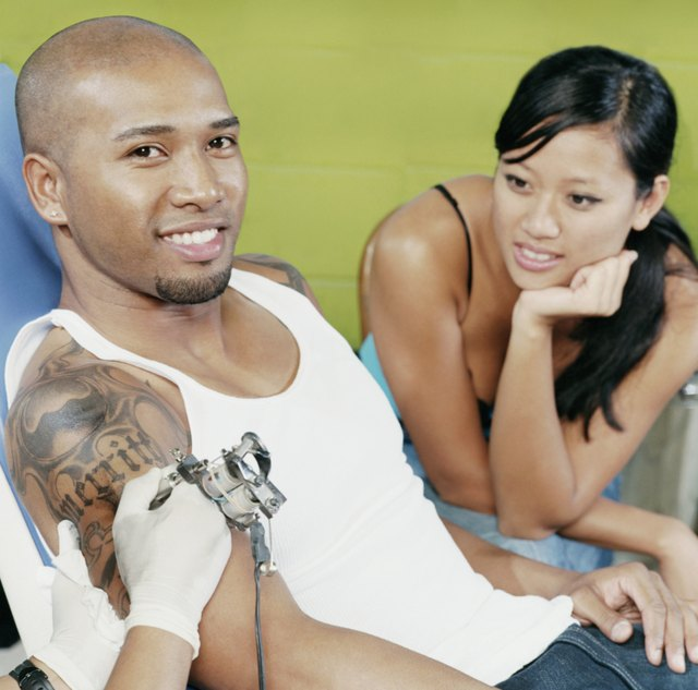 Young Man Having a Tattoo Done in a Tattoo Parlour and a Young Woman Watching