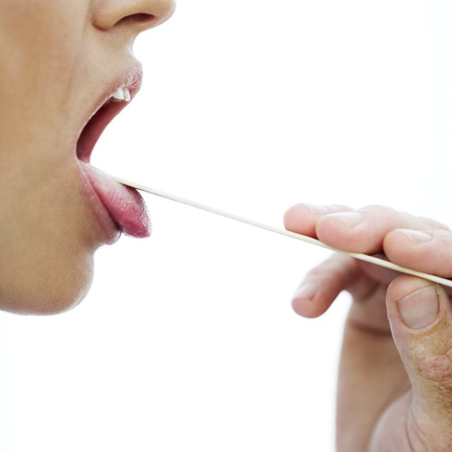 woman's throat checked with a tongue depressor