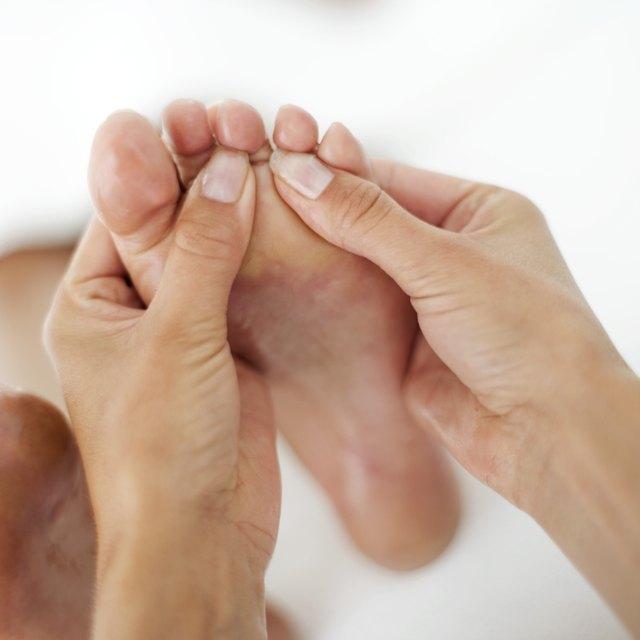 close-up of a masseuses' hands massaging a foot