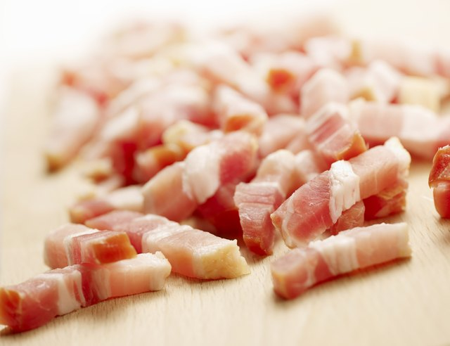 raw diced bacon on a wooden cutting board