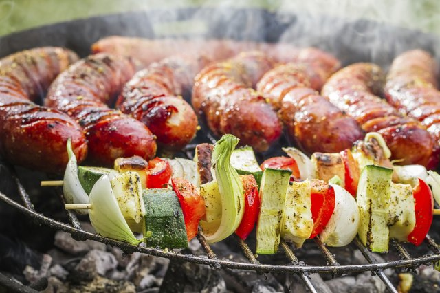 Closeup of sausages and skewers on the grill