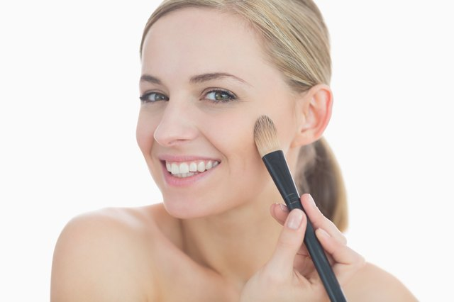Portrait of smiling young woman putting on make-up