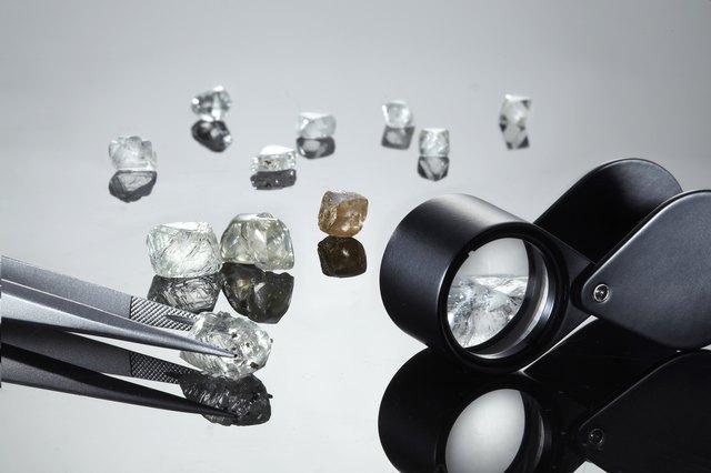 Uncut diamonds with tweezers and loupe