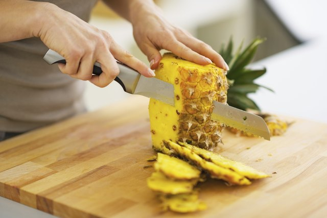 closeup on woman cutting pineapple