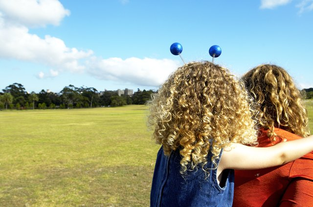 Woman giving daughter (3-5)  piggyback in park, rear view