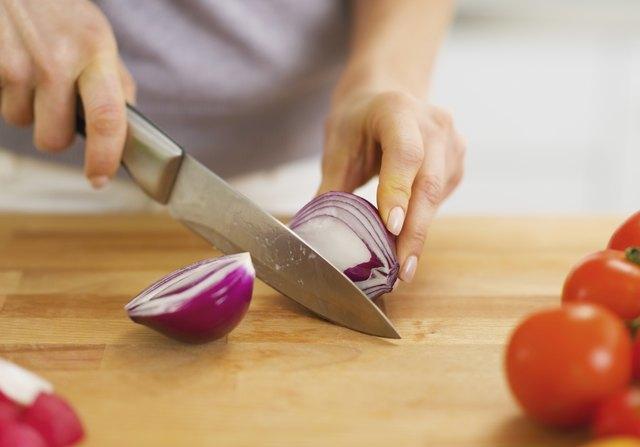 Closeup on woman cutting onion