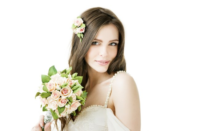Studio portrait of a young beautiful bride with a wedding bouquet
