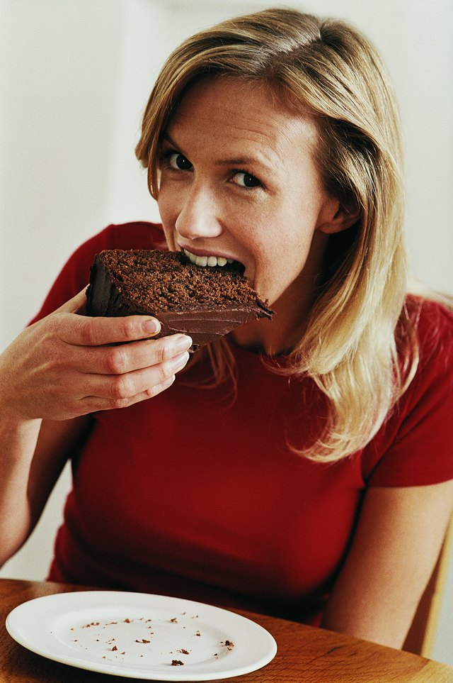 Woman Sitting at Table and Biting Into a Slice of Chocolate Cake