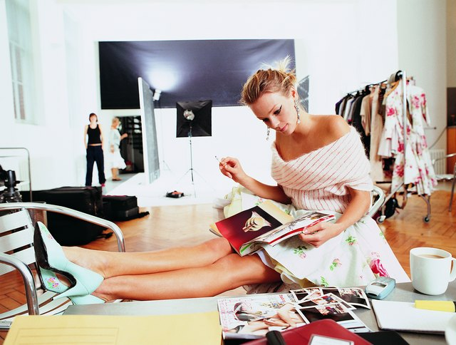 Side View of a Fashion Model Reading a Magazine With Her Feet Up in a Studio
