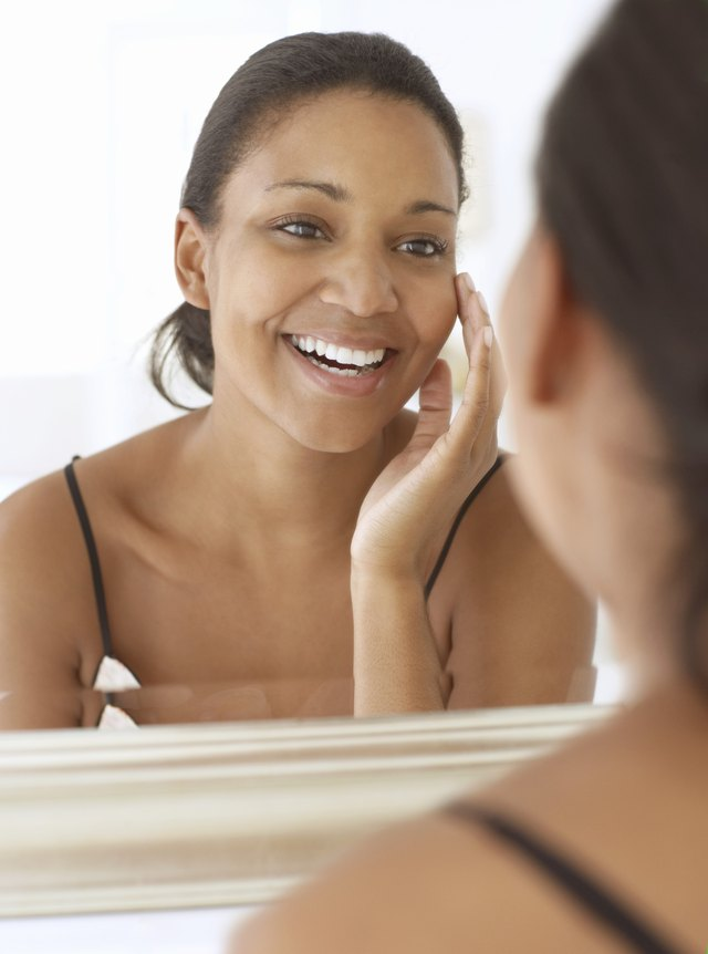 Young woman looking in mirror, touching face, smiling, close-up