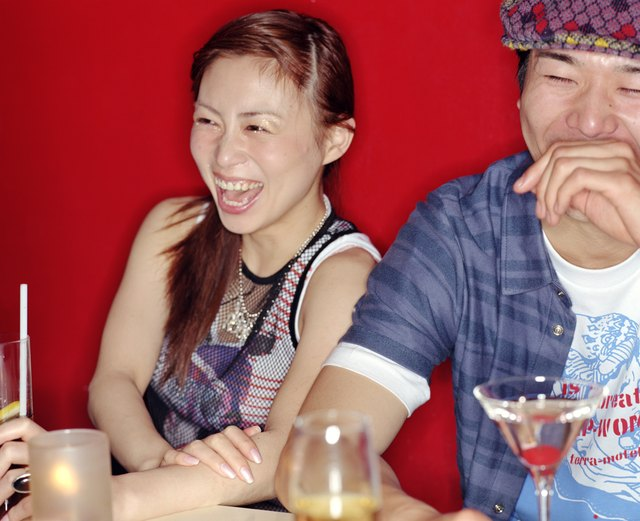 Young man and woman drinking cocktails in nightclub, laughing