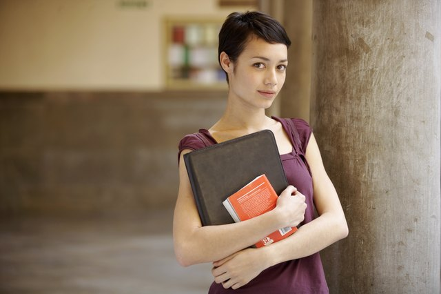 Young woman standing by column holding files, smiling, portrait