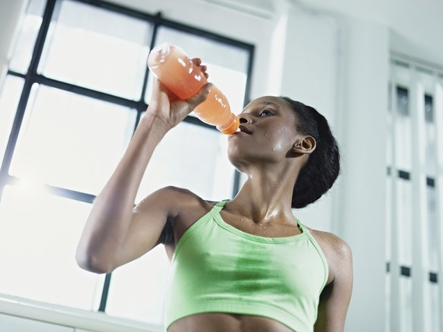african woman in gym drinking energy drink