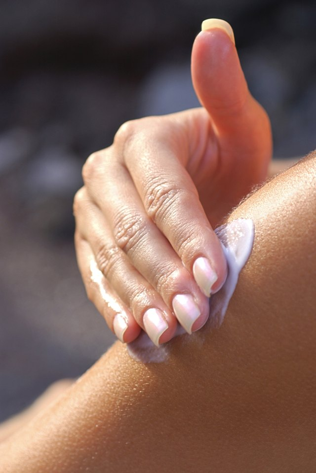 Close-up of a woman's hand applying lotion to her shoulder