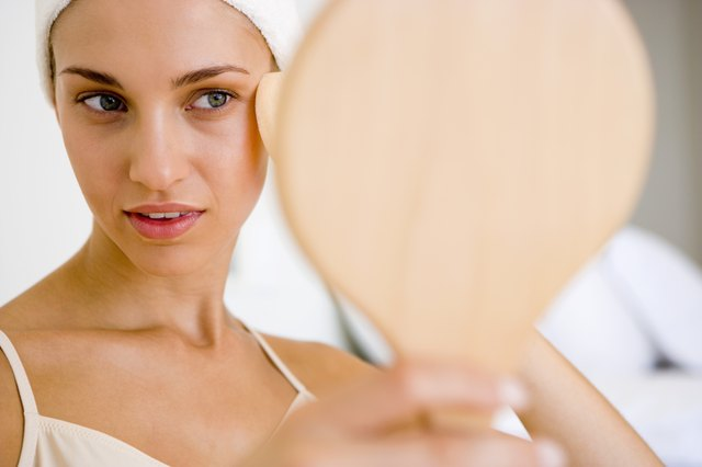Woman using hand mirror