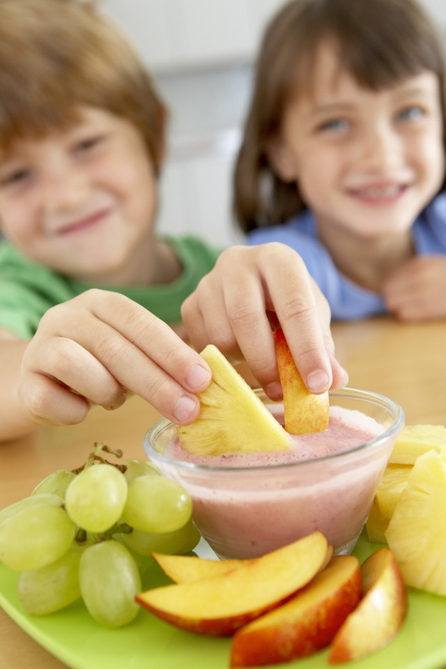 Children dipping fruit in yogurt