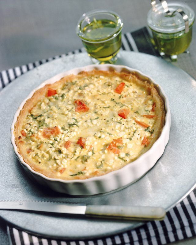 Fresh cheese quiche in tart pan with knife, close-up