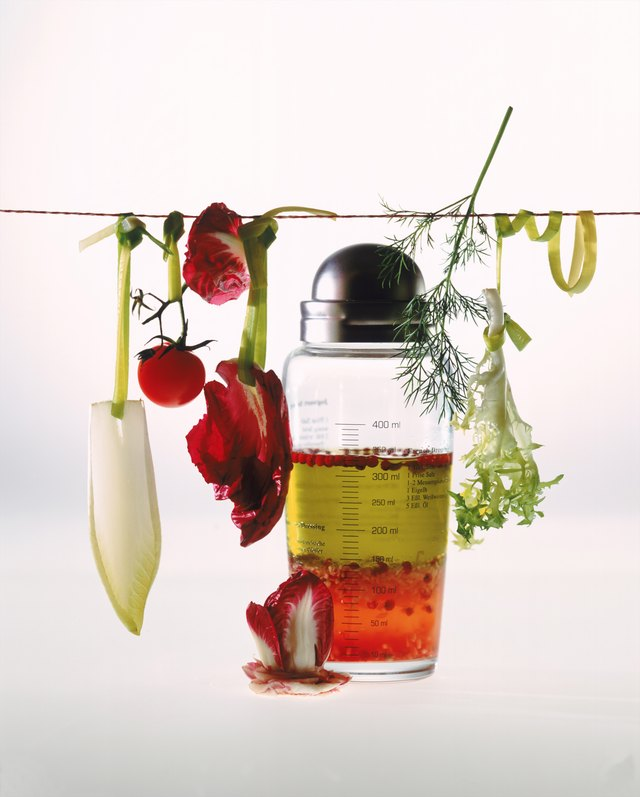 Salad dressing and jar of olive oil on white background, close-up