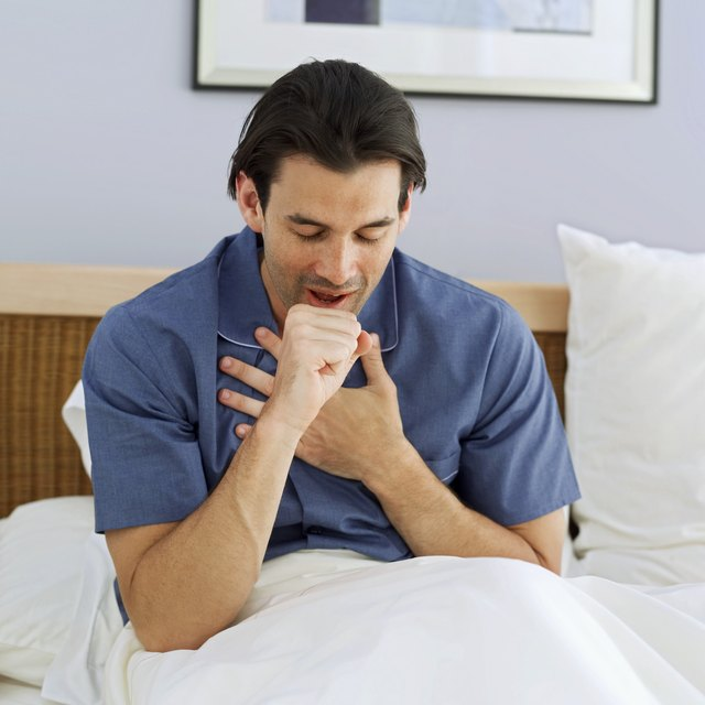 sick man lying in bed coughing