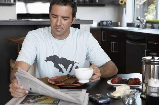Man eating breakfast, drinking coffee and reading newspaper