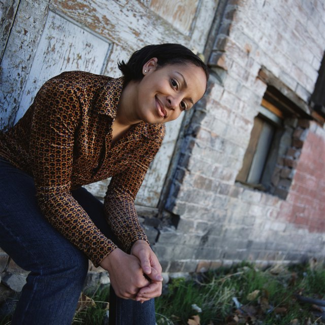 young woman in orange long sleeve shirt blue jeans sits on the doorstep of old abandoned building