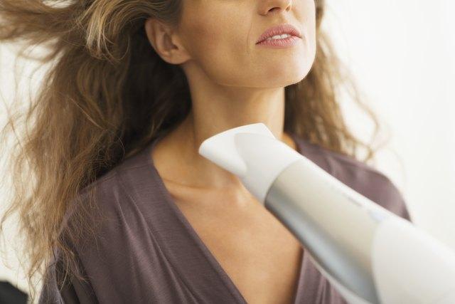 closeup on woman blow drying hair