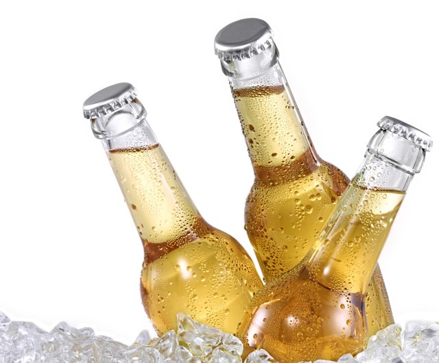 Three dewy beer bottles on ice
