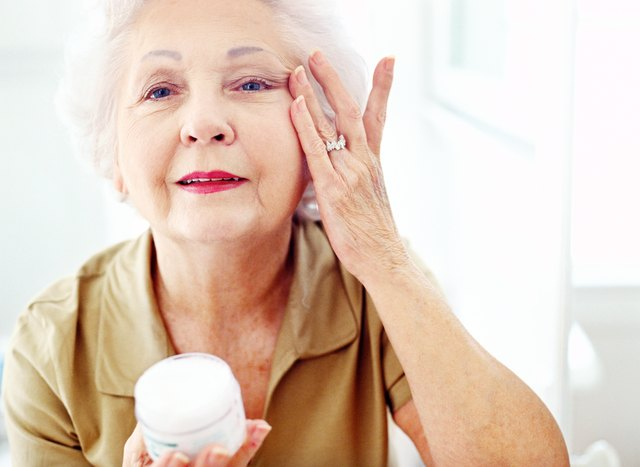 portrait of an elderly woman applying wrinkle cream