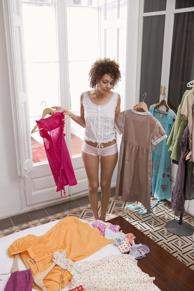 Woman in bedroom choosing clothes to wear
