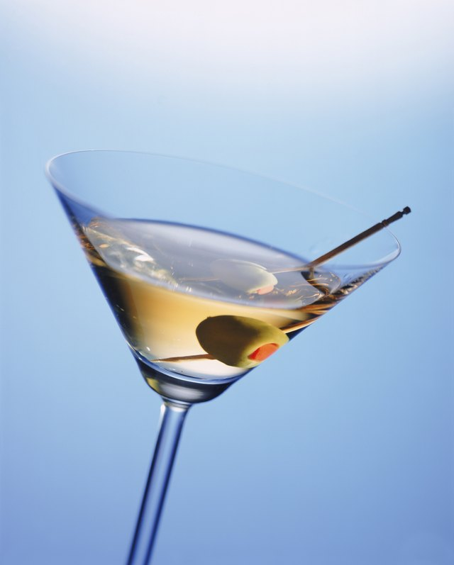 Martini glass with cocktail stick and green olive, close-up