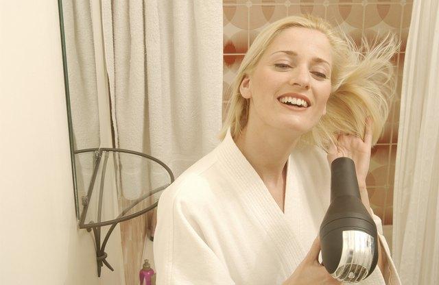 Smiling woman drying hair