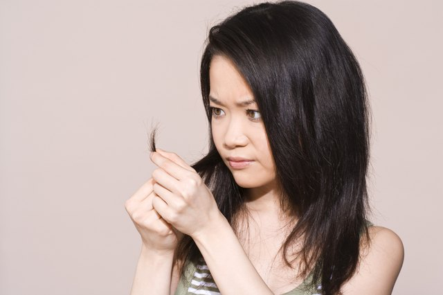 Woman inspecting split-ends