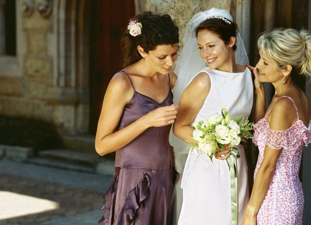 bride standing outside a church with her mother and a bridesmaid