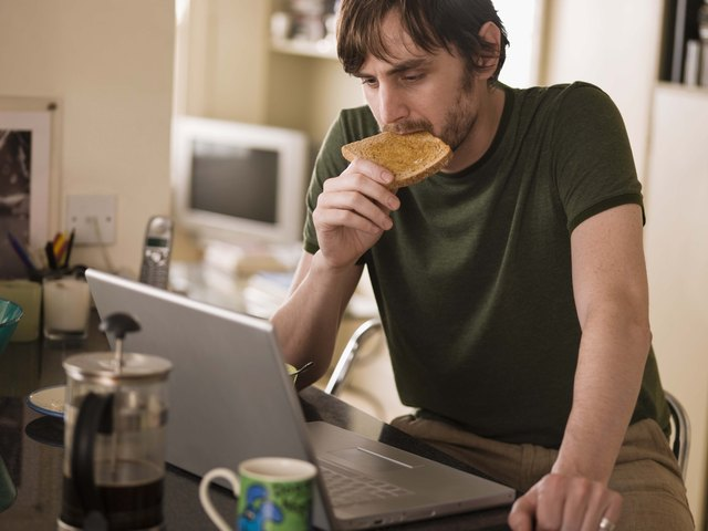 Man on laptop eating toast