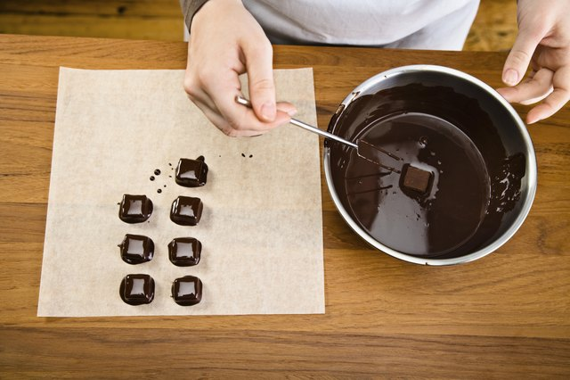 Dipping caramels into melted chocolate