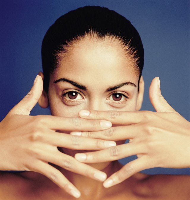 Woman hiding face behind hands