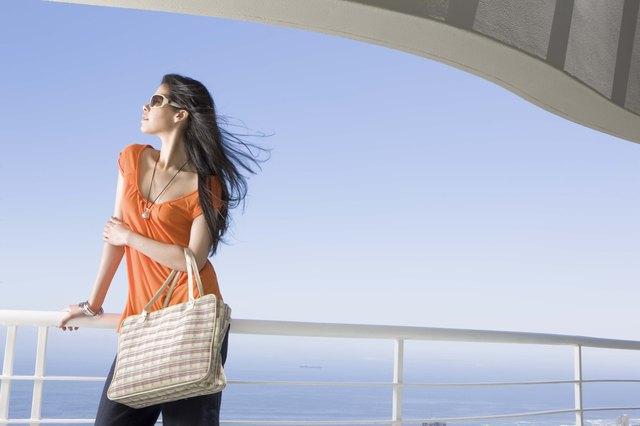 Fashionable woman with handbag standing on balcony