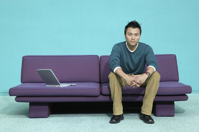 Portrait of a young man sitting on a couch with a laptop next to him