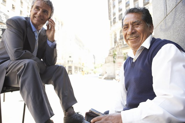 Senior man shining businessman's shoes in street, smiling, portrait
