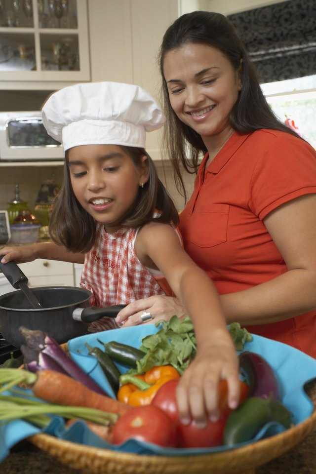 Side profile of a girl cooking with her mother