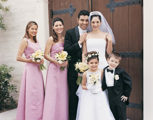 Bride and Groom Stand With Bridesmaids and Pageboy at the Door of a Church