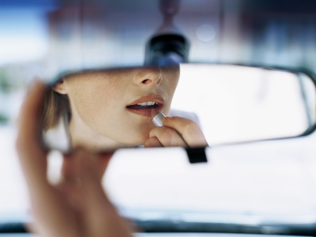 young woman applying lipstick in a car