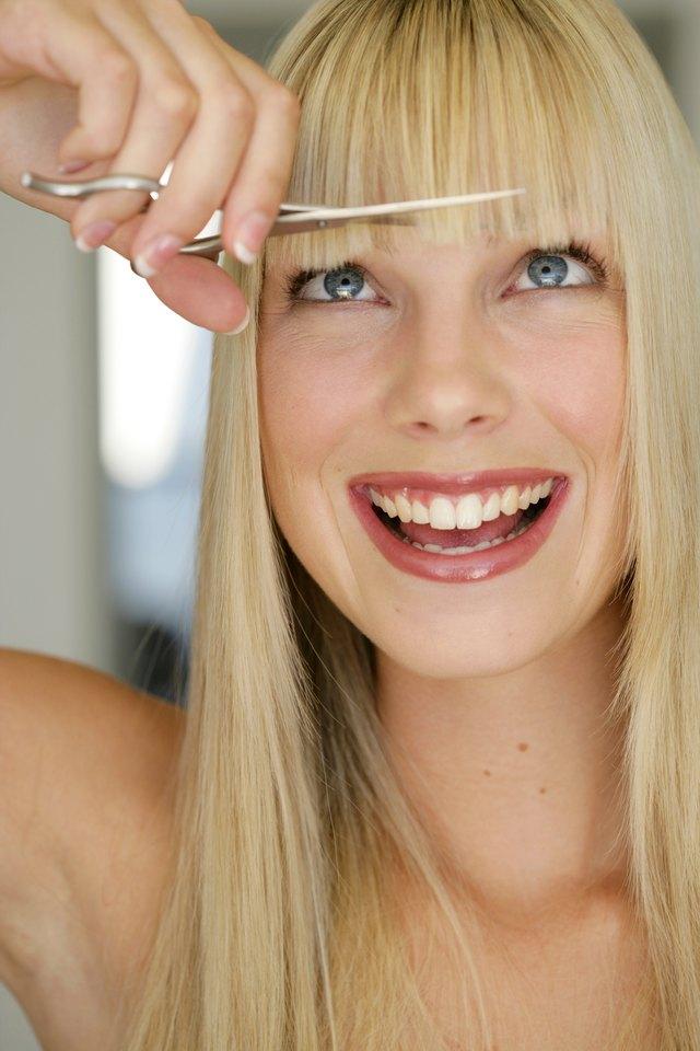 Woman trimming bangs