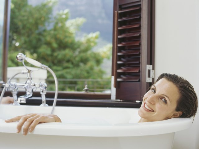 Portrait of a mid adult woman lying in a bathtub and smiling