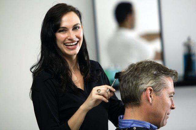 Woman cutting hair of man