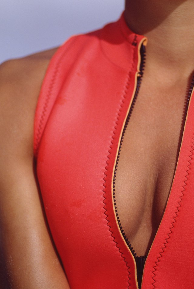 Young woman in unzipped vest, close-up, midsection
