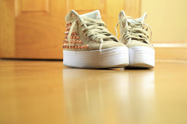 Pair of funky used sneakers shoes on hard wood floor