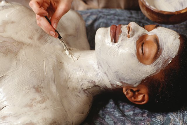 Woman having body wrap at health spa, close-up