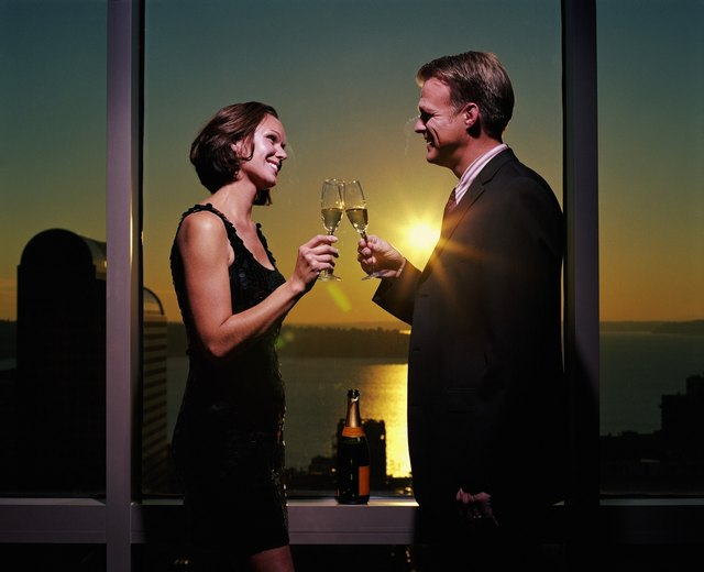 Couple standing beside window, raising toast with champagne, side view