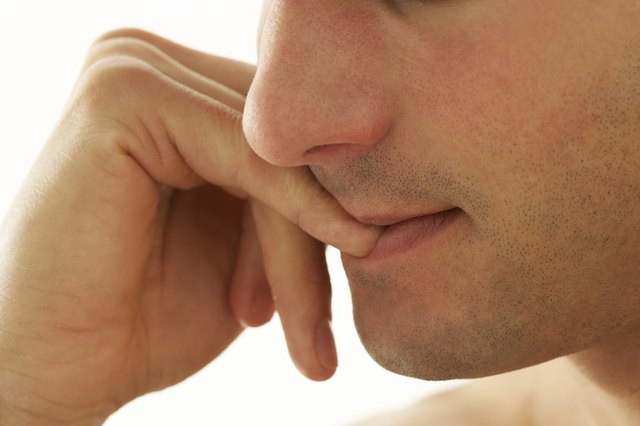 Young man biting nails, close-up